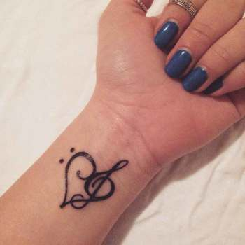 Little wrist tattoo of a bass clef and a treble...