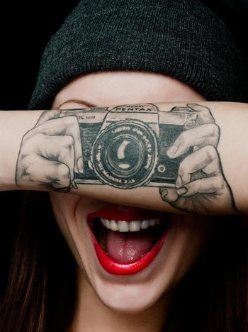 whimsical camera forearm tattoo for a shutterbug