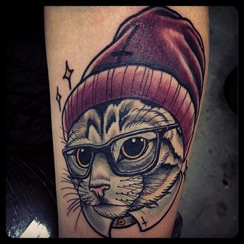 Cat with glasses and hat tattoo