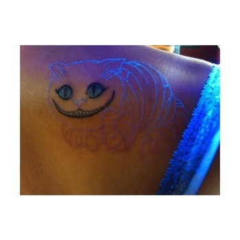 Tattoo of the Cheshire Cats face with the outline of the cat in white. The body glows in blacklight.