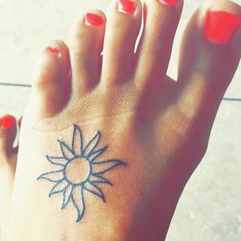 Small foot sun tattoo